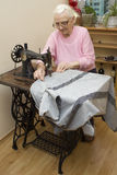 An old white hair woman sews on an old sewing machine. Tailoring of an old seamstress woman. The hands of an old seamstress woman cutting a thread at a machine Stock Images