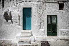 Old white house with door and window. Entry of an old Italian house. Example of architecture of the past. Ostuni, Italy Royalty Free Stock Image