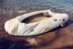 Old white inflatable flat boat washed up on the shore. Concept of risk and insurance royalty free stock images