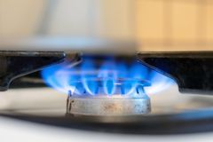 Old kitchen stove cook with blue flames burning. Can be a source of fire or explosion. Household gas stove. In kitchen room stock image