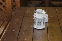 The old white lantern stands on a wooden table. stock photography
