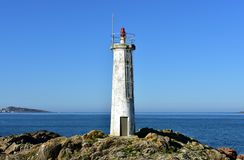 Old white lighthouse on the rocks with blue sea and sunny day. Galicia, Spain. royalty free stock photo