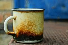 An old white metal mug charred in black soot stands on  table. An old white metal mug charred in black soot stands on a brown table royalty free stock image
