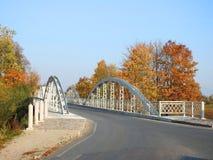 Old white metallic bridge, road and colorful trees, Lithuania stock photos
