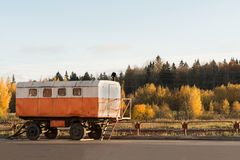 Old white orange construction trailers on a background of autumn forest Royalty Free Stock Photography