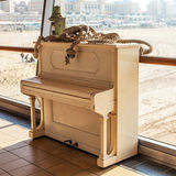 Old white piano on one pier of North Sea Royalty Free Stock Images
