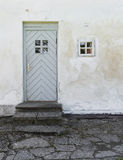The old white plastered wall with a small window and a door and Royalty Free Stock Photos