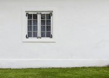 The old white plastered wall with a window and green lawn before Stock Photos