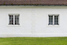 The old white plastered wall with a windows and green lawn befor Stock Photo
