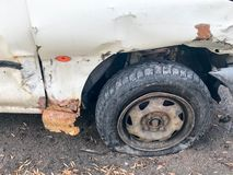 Old white rusty broken car of the carcass with lowered punctured wheels with scratches corrosion and a torn-off bumper. With dents and scratches thrown on the stock image