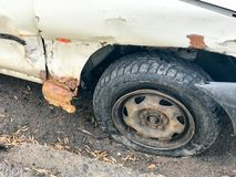 Old white rusty broken car of the carcass with lowered punctured wheels with scratches corrosion and a torn-off bumper with dents. And scratches thrown on the royalty free stock photography