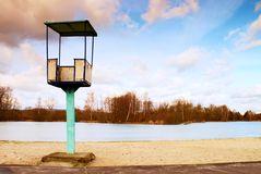 Old white and rusty metal lifeguard tower with chair on a beach. Frozen water level within witer. Time Stock Photo