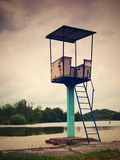 An old white and rusty metal lifeguard tower with chair on a lake beach. royalty free stock photo