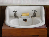 Old white sink and taps. Old white stained porcelain sink in a wooden stand, with hot and cold taps and a bar of soap Royalty Free Stock Image