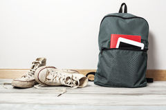 Old white sneakers with school bag on wooden background Stock Images