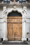 Old white stone entrance with statues and wooden portal. Royalty Free Stock Photos