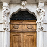 Old white stone entrance with statues and wooden portal. Stock Photos