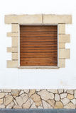 Old white stone wall with brown wooden shutters Royalty Free Stock Photo