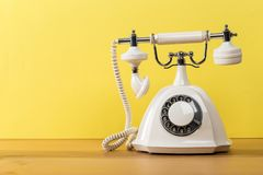 Old white telephone on wooden table with color wall background royalty free stock image