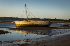 Old white vessel stranded on low tide Madagascar sunset Royalty Free Stock Images