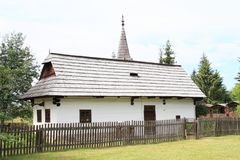 Old white village house in open-air museum. Old white village house with shingles roof with wooden fence in front of and pine trees behind in open-air museum Stock Images