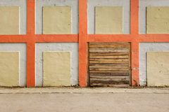 Old White Wall With Checkered Pattern Detail and wooden doorway Royalty Free Stock Photos
