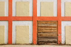 Old White Wall With Checkered Pattern Detail and wooden doorway Royalty Free Stock Photo