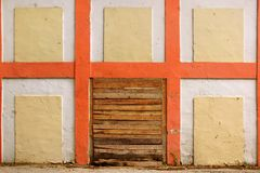Old White Wall With Checkered Pattern Detail and wooden doorway Stock Image