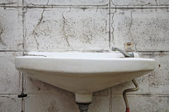 Old white washbasin on dirty wall Royalty Free Stock Image