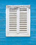Old white window with wooden shutters. Old white window with wooden shutters on the blue wall of boards Stock Photos