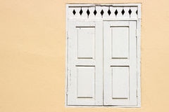 Old White window with yellow wall Royalty Free Stock Images