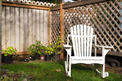 Old, white, wood and empty adirondack chair in a cozy, private g Stock Photos