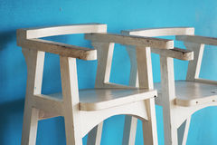 Old white wooden chair with blue wall Royalty Free Stock Photos