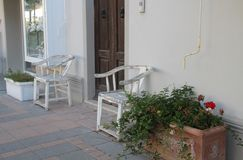 Old white wooden chairs and flowerpots with flowers stock photography