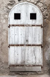 Old white wooden door with arch in stone wall Royalty Free Stock Image