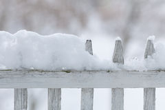 Old white wooden fence covered with snow. Winter seasonal specific. Stock Image