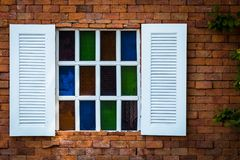 Old white wooden window with stained glass on brown brick wall background,. Stone wall with little colorful stained glass window and green leaf on the right Royalty Free Stock Images