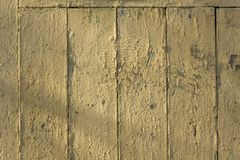 Old white yellow beige fence wall of wooden boards with cracked paint, vertical and horizontal lines and shadows. rough surface. A Old white yellow beige fence royalty free stock photo