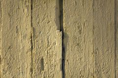 Old white yellow beige fence wall of wooden boards with cracked paint, vertical lines and shadows. rough surface texture. A old white yellow beige fence wall of stock photos