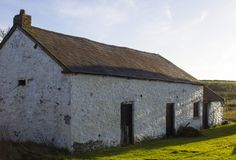 An old whitewashed stone built Irish Cottage with a small annex roofed with bangor Blue roofing tiles and rusting corrugated tin s. Heets. This was a typical Stock Photography