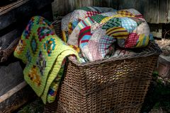 Old wicker basket filled with hand made quilts and blankets royalty free stock image
