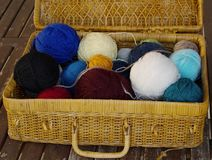 An old wicker basket with the open lid, with the remaining wool rolls Royalty Free Stock Photo