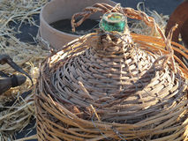 Old wicker bottle and glass Stock Image