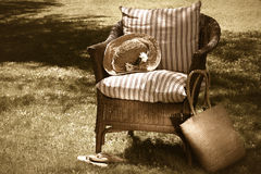 Old wicker chair/ sepia tone. Wicker chair and old summer hat on a hot summer's day royalty free stock photos