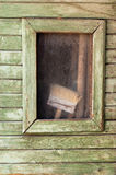 Old wide paint brush behind small window against ragged wooden wall Royalty Free Stock Photos