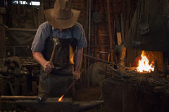 Old Wild West Blacksmith Hammering Royalty Free Stock Image