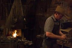 Old Wild West Blacksmith. Blacksmith working with iron in an old wild west blacksmith shop Royalty Free Stock Photos