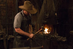 Old Wild West Blacksmith Hammering Royalty Free Stock Photo