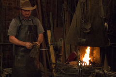 Old Wild West Blacksmith. Blacksmith working with iron in an old wild west blacksmith shop royalty free stock photos