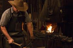 Old Wild West Blacksmith Hammering. Blacksmith working with iron in an old wild west blacksmith shop Stock Photography